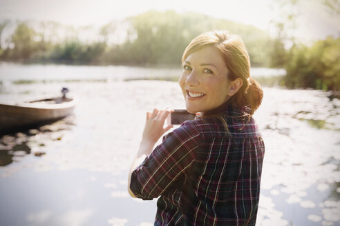 Portrait smiling woman with red hair photographing sunny lake with camera phone - CAIF10737