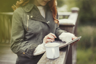 Woman drinking coffee using digital tablet at balcony railing - CAIF10740