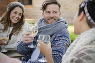 Smiling friends drinking wine on patio - CAIF10743