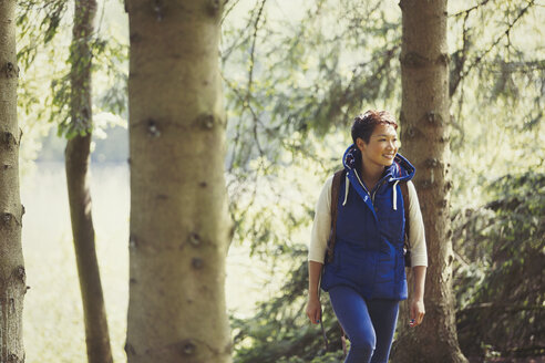 Smiling woman hiking in woods - CAIF10746