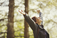 Exuberant woman hiking in sunny woods with head back and arms raised - CAIF10749