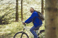 Smiling man riding mountain biking in woods - CAIF10755