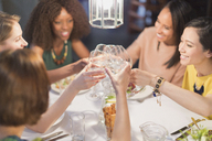 Smiling women friends toasting white wine glasses dining at restaurant table - CAIF10785