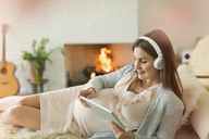 Pregnant woman with digital tablet and headphones listening to music near fireplace - CAIF10806