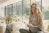 Portrait smiling pregnant woman eating ice cream - CAIF10812
