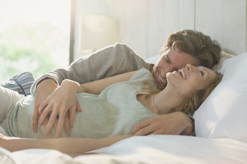 Affectionate pregnant couple laying in bed laughing - CAIF10821