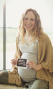 Portrait smiling pregnant woman holding ultrasound - CAIF10833