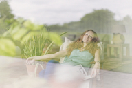 Comfortable woman relaxing in armchair at living room window - CAIF10839