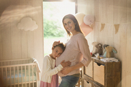 Portrait smiling pregnant mother and daughter in nursery - CAIF10842