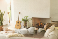 Serene pregnant woman laying on chaise next to fireplace in living room - CAIF10848