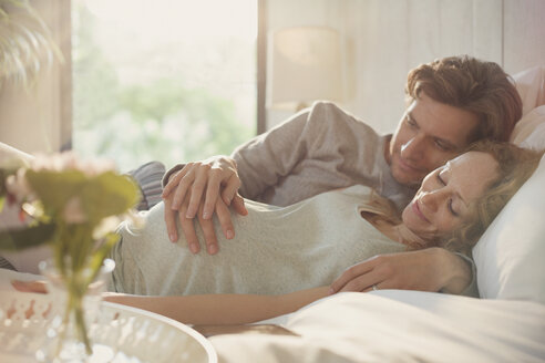 Serene pregnant couple holding stomach on bed - CAIF10860