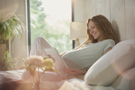Smiling pregnant woman using digital tablet on bed in sunny bedroom - CAIF10878