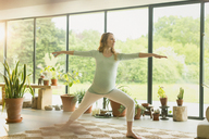 Pregnant woman practicing yoga warrior 2 pose - CAIF10881