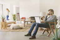 Man talking on cell phone and using laptop in living room - CAIF10896