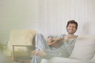 Smiling man in pajamas playing guitar in living room - CAIF10911