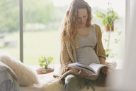 Pregnant woman reading book - CAIF10914