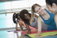 Smiling women practicing side plank in exercise class gym studio - CAIF10953