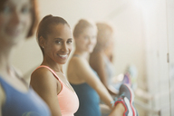 Portrait smiling women stretching legs at barre in exercise class gym studio - CAIF10956