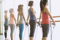 Women exercising with resistance bands at barre in exercise class gym studio - CAIF10962