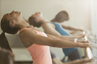 Women stretching in backbend at barre in exercise class gym studio - CAIF10965