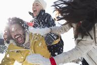 Friends enjoying snowball fight - CAIF10992