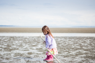 Girl with stick playing on beach - CAIF11058
