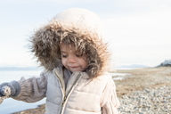 Girl in fur hood jacket walking on beach - CAIF11061