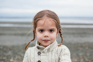 Portrait of serious girl with braided pigtails on beach - CAIF11064
