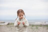 Curious girl examining pebbles on beach - CAIF11067