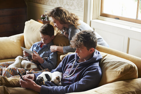 Brothers and sister using digital tablet and cell phone with puppies in laps - CAIF11076
