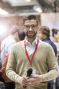 Portrait smiling speaker with microphone at technology conference - CAIF11097