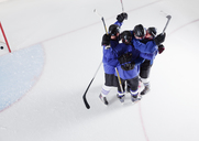 Hockey team in blue uniforms cheering celebrating on ice - CAIF11145