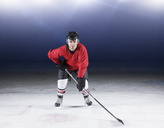 Portrait determined hockey player in red uniform on ice - CAIF11148