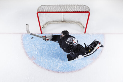 Overhead view hockey goalie reaching to block puck at goal net - CAIF11151