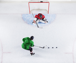 Overhead view hockey player practicing with goalie shooting puck at goal net - CAIF11163