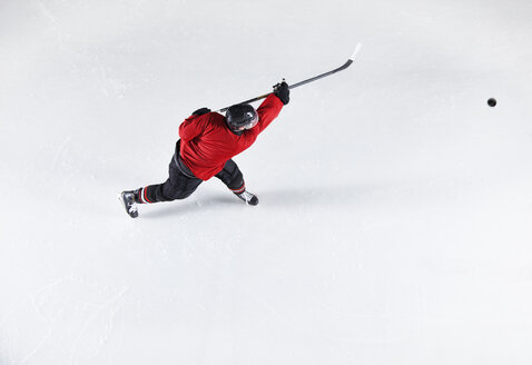 Hockey player in red uniform shooting puck on ice - CAIF11175