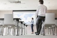 Businessman watching businesswoman leading presentation at projection screen in conference room - CAIF11190
