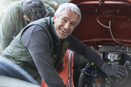 Portrait smiling mechanic fixing engine in auto repair shop - CAIF11211
