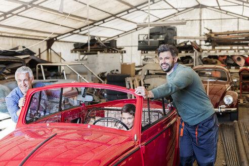 Smiling mechanics pushing boy in classic car in auto repair shop - CAIF11235