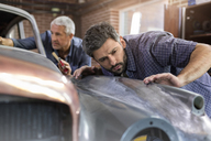 Focused mechanic examining classic car panel in auto repair shop - CAIF11238