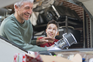 Smiling father and son fixing car engine in auto repair shop - CAIF11241