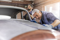 Focused mechanic examining classic car panel in auto repair shop - CAIF11244