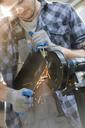Metal worker using sander in workshop - CAIF11253