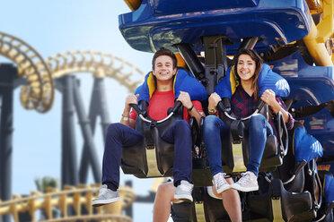 Young couple riding amusement park ride - CAIF11301