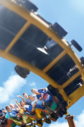 Friends riding roller coaster at sunny amusement park - CAIF11304