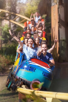 Portrait enthusiastic friends cheering and riding roller coaster at amusement park - CAIF11331