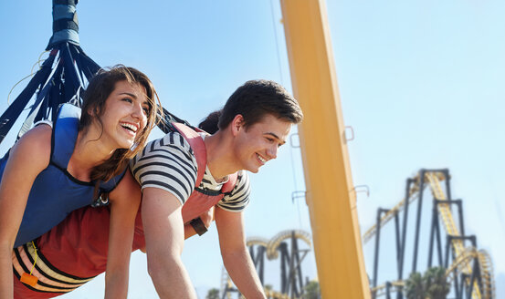 Enthusiastic friends bungee jumping at amusement park - CAIF11334