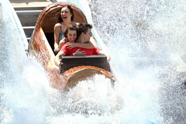 Enthusiastic friends getting splashed in water log amusement park ride - CAIF11337