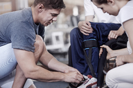 Physical therapist tying man's shoe - CAIF11343
