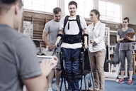 Physical therapists guiding man walking - CAIF11352